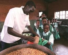 Marathon Champ Paul Tergat, a WFP School Meals Ambassador, distributing food in Kenya. (WFP/Francesco Broli)